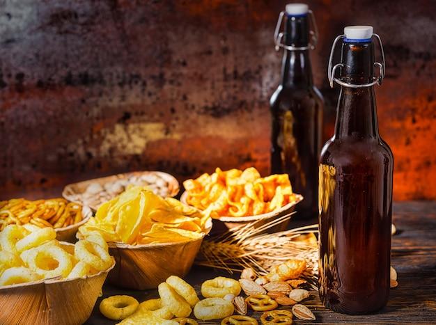 Holzteller mit snacks in der nähe von zwei flaschen bier, weizen, verstreuten nüssen und brezeln auf dunklem holzschreibtisch. lebensmittel- und getränkekonzept