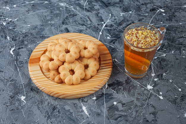 Holzteller mit süßen blütenförmigen keksen und einer tasse tee auf marmoroberfläche.