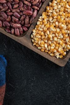 Holzteller mit ungekochten roten kidneybohnen und popcorn.
