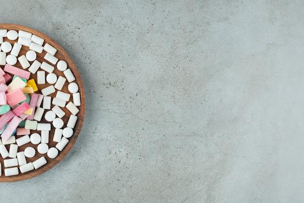 Holzteller mit vielen kaugummis auf steinoberfläche.
