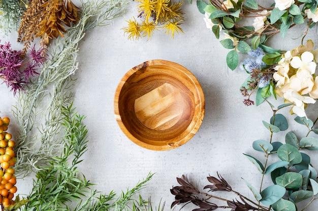 Holzteller und botanische ornamente auf einem marmortisch