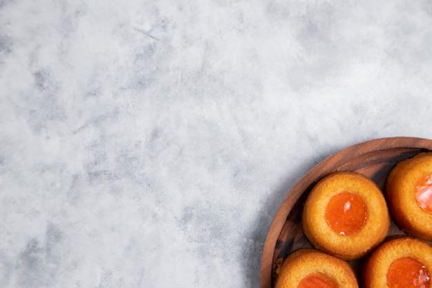 Holzteller voll von hausgemachten aprikosenmarmelade fingerabdruck kekse.