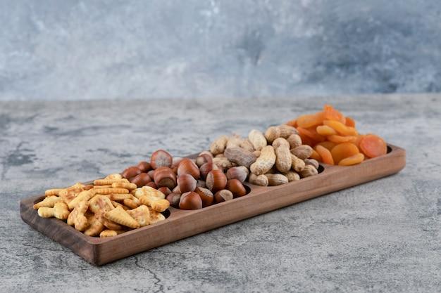 Holzteller voller nüsse, cracker und getrockneter aprikosen auf marmoroberfläche.
