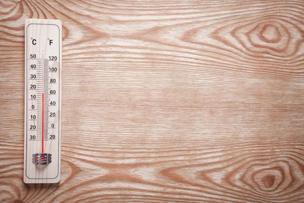 Holzthermometer auf hölzernem hintergrund
