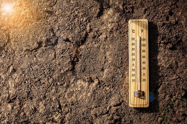 Holzthermometer, kalibriert in grad celsius und fahrenheit am heißen tag. - konzept der globalen erwärmung und des wetters.