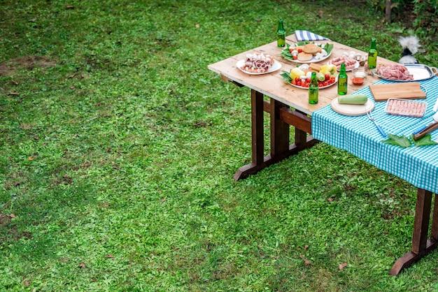 Holztisch auf einem rasen mit lebensmittel und getränk