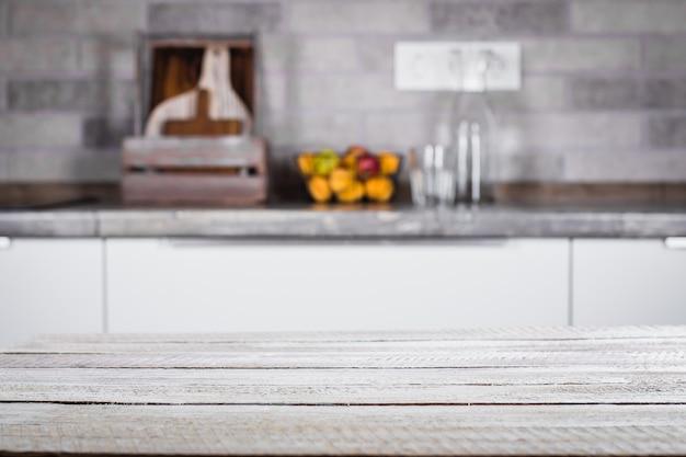 Holztisch auf hintergrund des küchenraumes. platz für objekt, text.