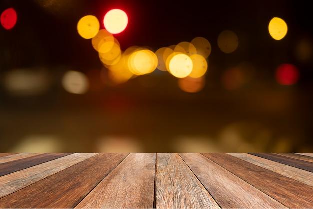 Holztisch des brauns im vorderen unscharfen hellen bokeh hintergrund gemasert