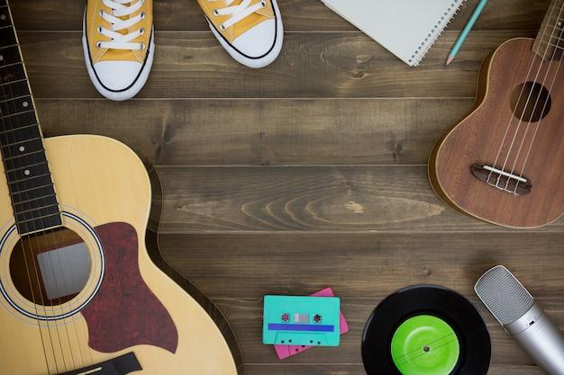 Holztisch des musikkomponisten, gitarre, ukulele, notizbuch, audiokassetten, mikrofon, tonbandgerät