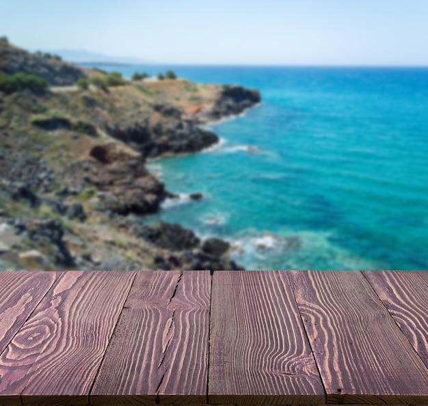 Holztisch draußen mit meerblick am schönen sommertag.
