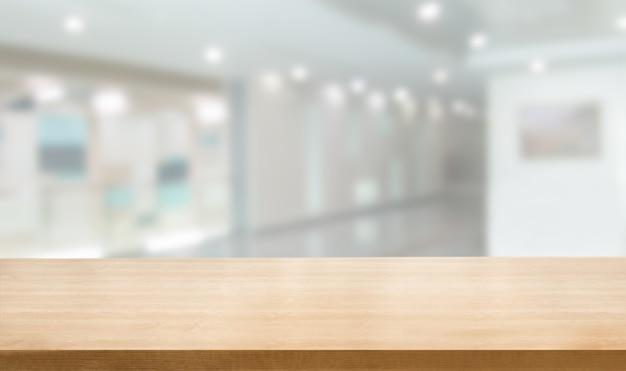 Holztisch im modernen krankenhausinnenraum mit leerem kopienraum auf dem tisch für produktanzeige