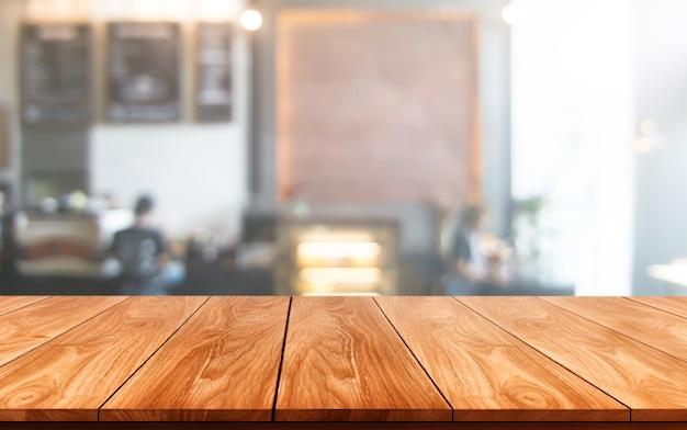 Holztisch im verschwommenen hintergrund des modernen restaurantraums oder des kaffeehauses für produktanzeigemodell.