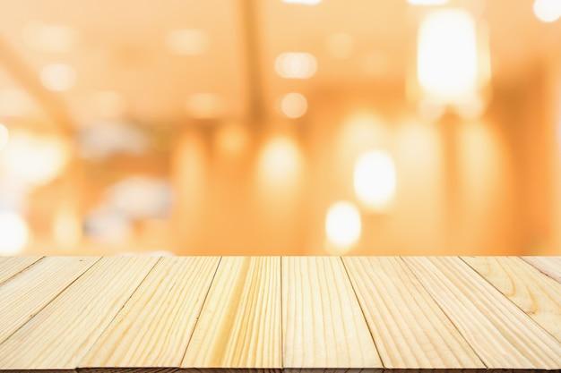 Holztisch mit abstraktem verschwommenem café-restaurant mit defokussiertem hintergrund der bokeh-lichter