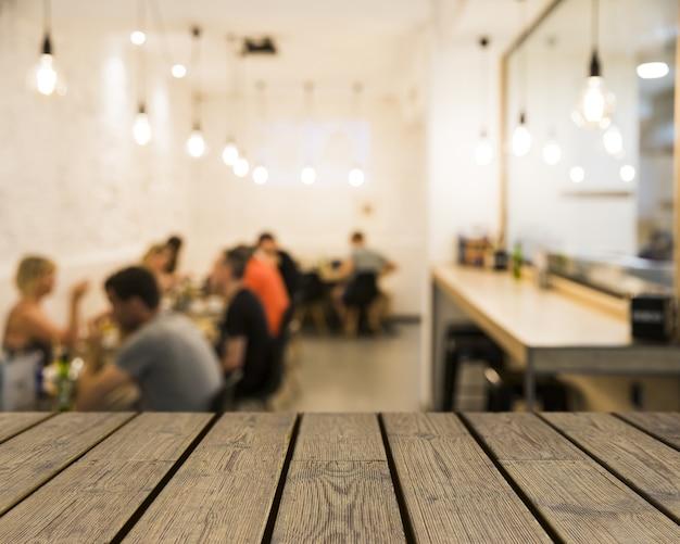 Holztisch mit blick auf menschen in mensa