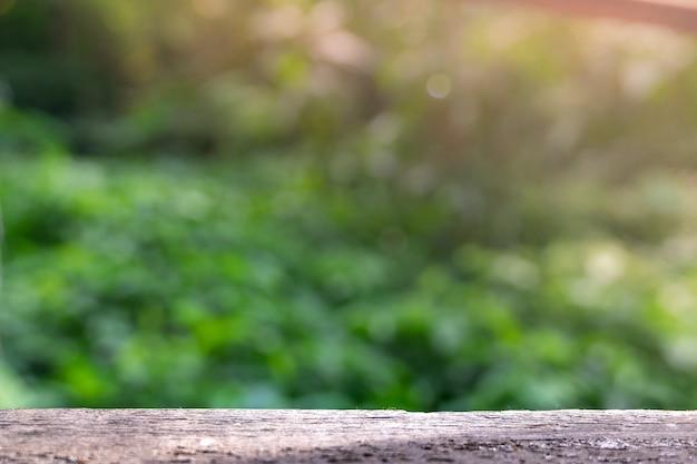 Holztisch mit freiem raum und unscharfer grüner baumhintergrund