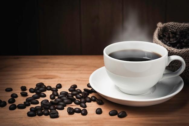 Holztisch mit kaffee. kaffeebohnen und kaffeetasse auf holzraum mit kopierraum.
