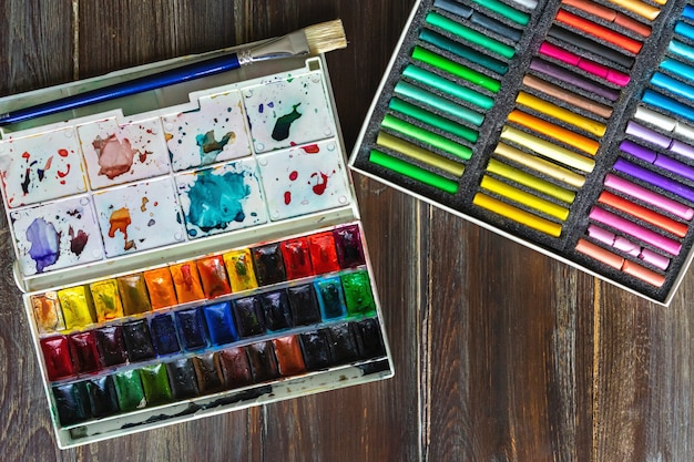 Holztisch mit pinseln, aquarellfarben und pastellkreide