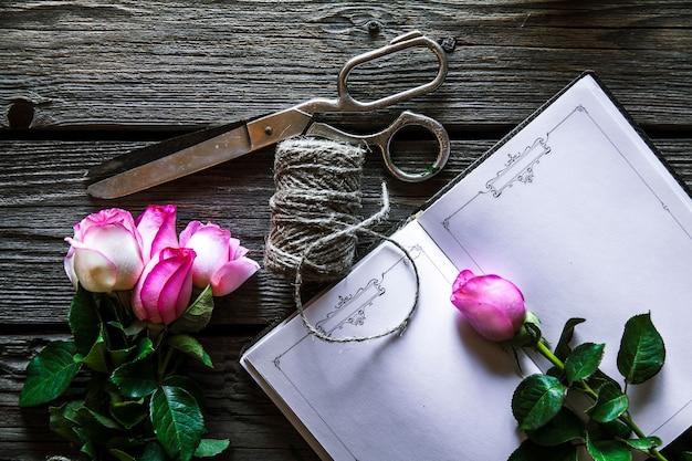 Holztisch mit rosen, notizbuch, faden und schere