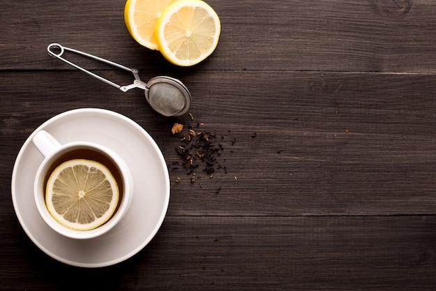 Holztisch mit schwarzem tee, zitrone und honig