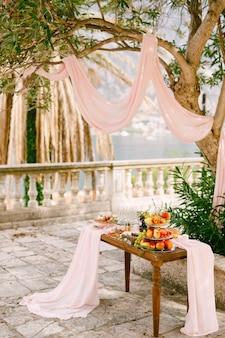 Holztisch mit stoff dekoriert mit einem regal für obst und köstlichkeiten im innenhof