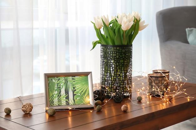 Holztisch mit strauß tulpen und dekoren im wohnzimmer