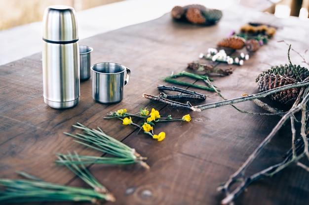 Holztisch mit thermoskanne, kaffeetassen und wort mit naturobjekten