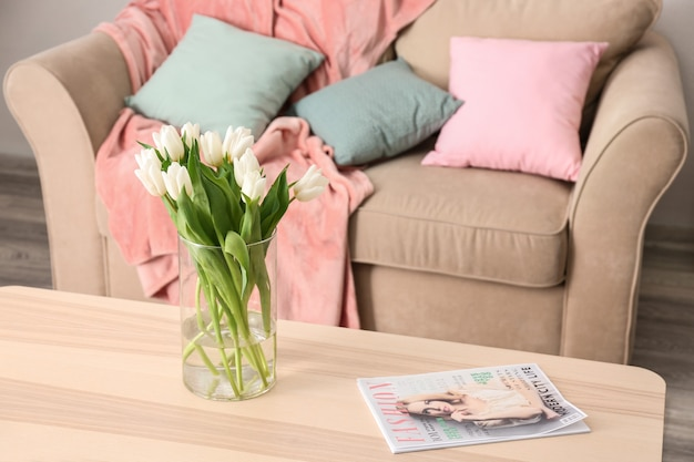 Holztisch mit tulpenstrauß in der nähe des sofas im wohnzimmer