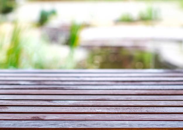 Holztisch mit unscharfem bokeh natürlichem hintergrund.