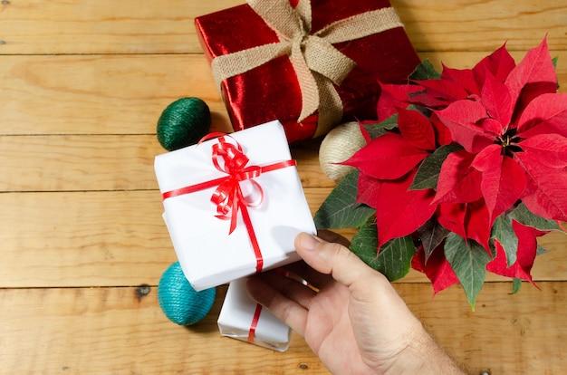 Holztisch mit weihnachtsgeschenken und weihnachtsstern personenhände