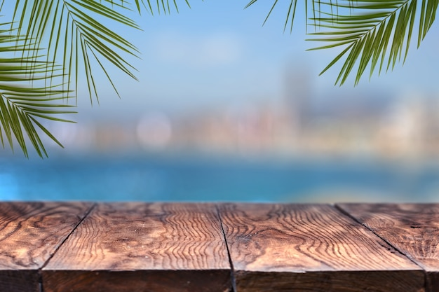 Holztisch oder holz mit palmen gegen die einer verschwommenen stadt. natürlich mit kopierraum.