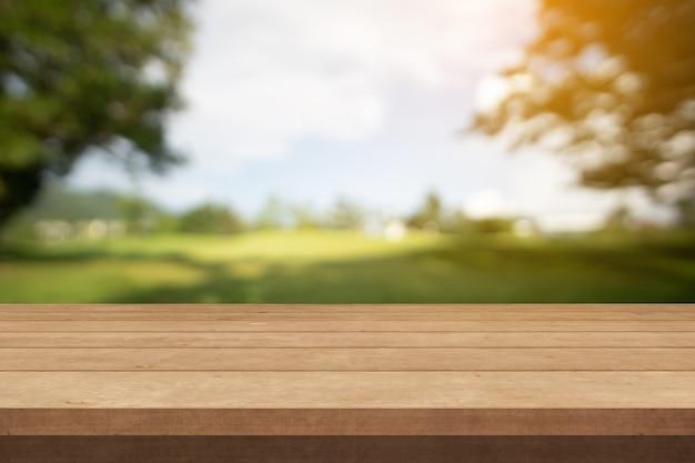 Holztisch oder holzterrasse und grüner garten in der sommersonne