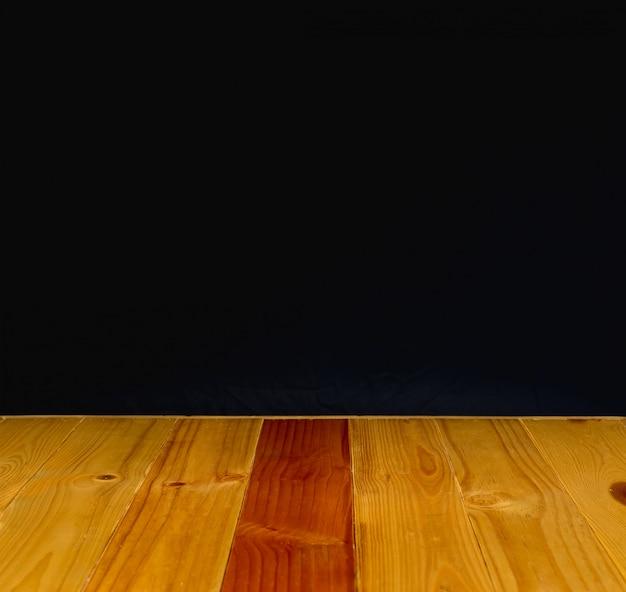 Holztisch oder schreibtisch mit schwarzem wandhintergrund.
