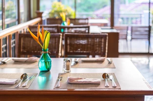 Holztisch stellte für mahlzeit im restaurant mit gemütlichem innenraum, frühstückszeit ein.