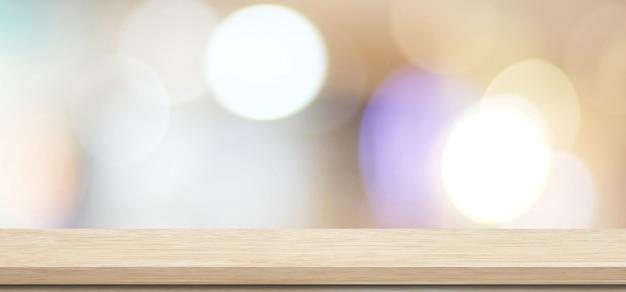 Holztisch, tischplatte, schreibtisch über unschärfespeicher mit bokeh lichthintergrund, leeres hölzernes regal, zähler, schreibtisch für einzelhandelsgeschäftprodukt-anzeigenhintergrund