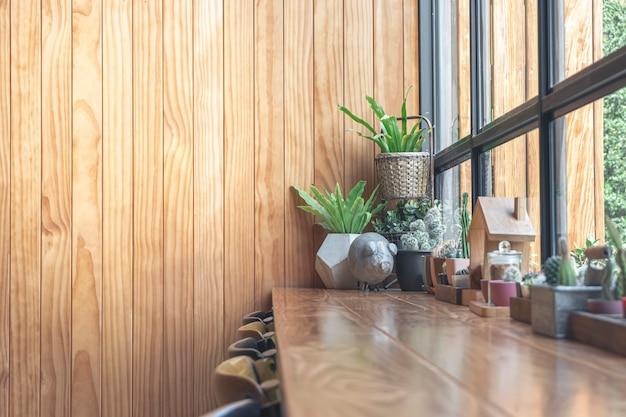 Holztisch und kaktus auf dem tisch in der kaffeestube, hölzerner hintergrund