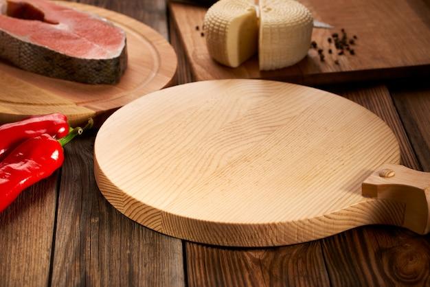 Holztisch und rundes schneidebrett, umgeben von lebensmitteln