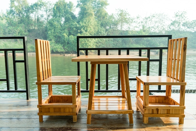 Holztisch und stuhl auf der terrasse in der nähe des flusses
