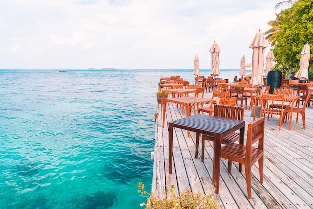 Holztisch und stuhl mit meerblick auf den malediven