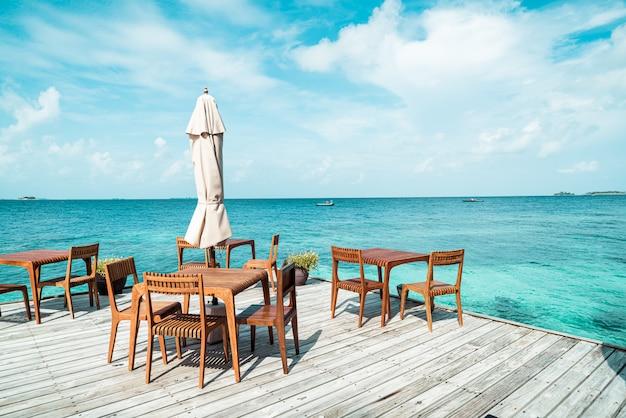 Holztisch und stuhl mit meerblickhintergrund in malediven