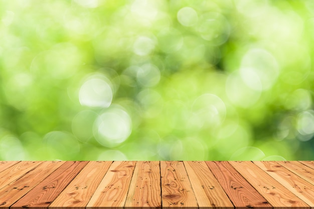Holztisch- und unschärfenaturbaum-grünhintergrund für frühling oder sommerkonzept.