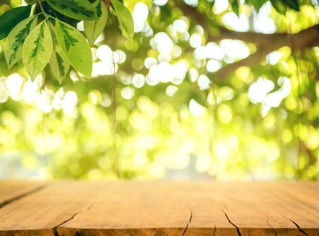 Holztisch und unscharfer frühlingshintergrund. frühlingskonzept mit grüner natur im freien.