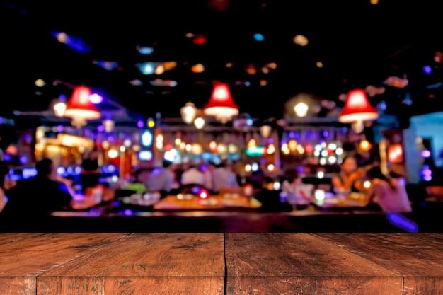 Holztisch vor abstraktem unscharfem hintergrund von restaurantlichtern