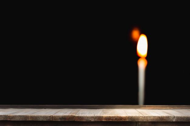 Holztisch vor der hellen kerze der unschärfe, die hell im schwarzen brennt