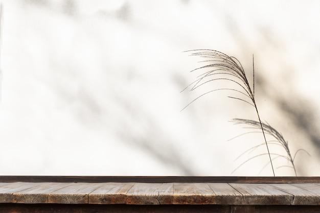 Holztisch vor grasblume mit schatten auf weißem hintergrund.