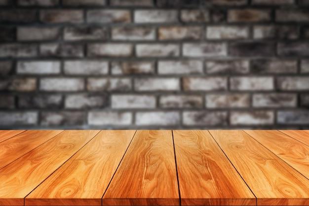 Holztisch vor rustikalem backsteinmauer-unschärfehintergrund mit leerem kopienraum auf dem tisch.