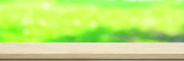 Holztisch, zählerhintergrund, weißes hölzernes regal und verwischen grüne baumnatur für nahrungsmittelpicknick, küchenproduktanzeigehintergrund