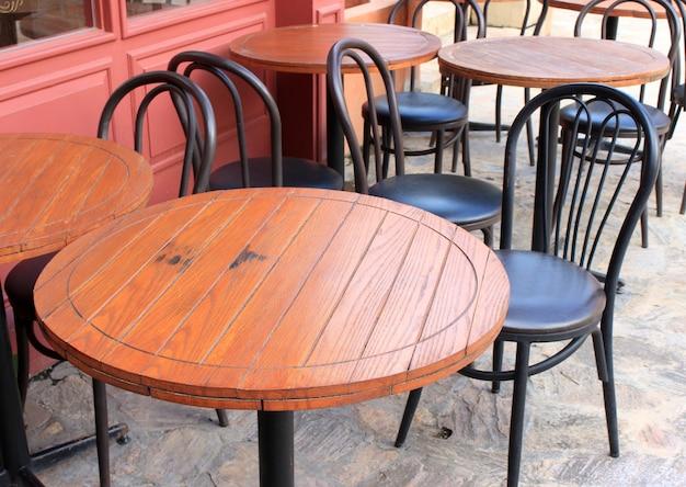 Holztische und schwarze stühle fürs mittagessen vor dem café