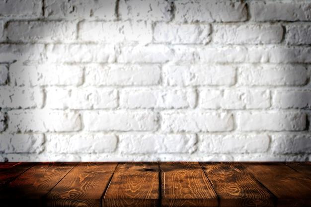 Holztischhintergrund und weiße backsteinmauer im hintergrund leere braune holztischplatte für pro