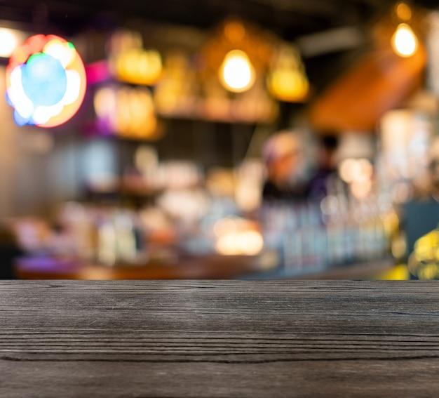 Holztischoberseite auf unscharfer szenenzählerstange in der kaffeestube