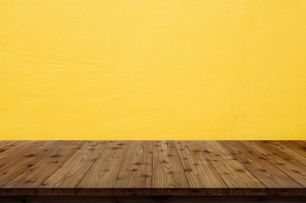 Holztischplatte auf gelbem wandhintergrund.
